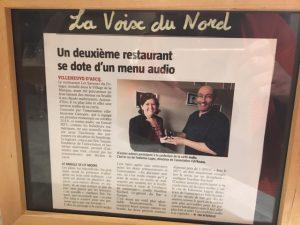 Article dans le restaurant expliquant l'accessibilité aux non-voyants au menu du restaurant et citant le soutien de FabAccess